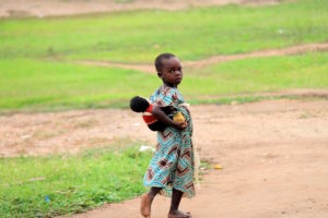 Little girl copies mummy carrying her doll on her back