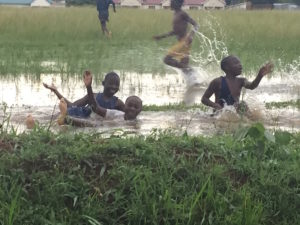 Having fun after a torrential downpour, flooding roads and playing fields.