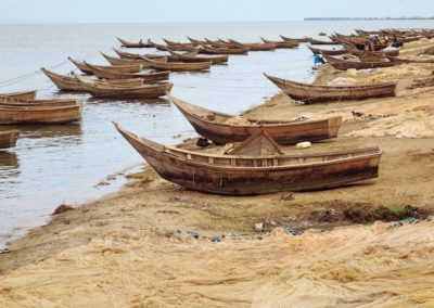Traditional boats line the shore, they are used for fishing in Uganda, usually man powered but sometimes with an outboard motor